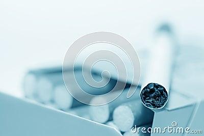 Cigarette lying on pack (blue toned)