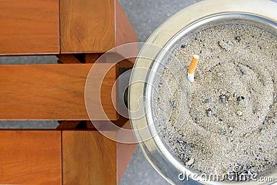 Cigarette in sand ashtray bin