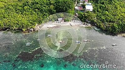 Cinematic-Drohnenschuss aus einer kleinen Sandbucht mit Booten, Gängen, Korallenriff und Urwald stock video footage