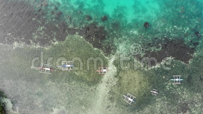 Cinematic Drohnenschuss von Fischerbooten in einem türkisfarbenen, transparenten Meer mit Korallenriffen und einer tiefen blauen  stock video footage