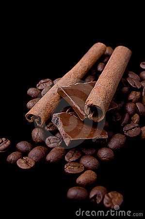 Cinnamon sticks over coffee beans and chocolate