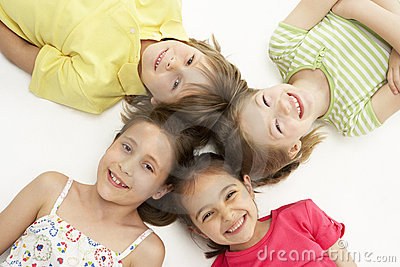 Circle of four young friends lying down smiling