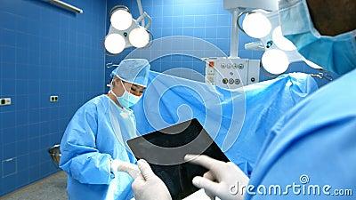 Cirurgião que usa a tabuleta digital quando paciente de funcionamento do colega de trabalho na sala de operação filme