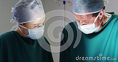 Cirurgiões que interagem um com o otro ao executar a operação na sala de operação filme
