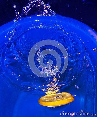 Citrus fruit slice fallen in water