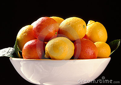 Citrus fruits in plate on black background
