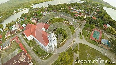 Città di Poblacion di vista aerea con la chiesa cattolica nelle Filippine Anda video d archivio