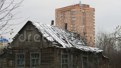 City, old house amid new multistory. One-storey wooden old house, in front of the new building stock video