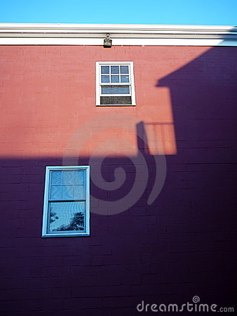 City: sunset building shadow on red wall