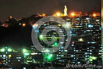Cityscape van de nacht met standbeeld bij heuveltop