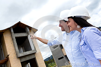 Civil engineers pointing at a house