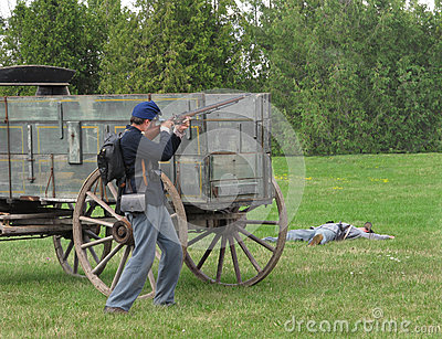 Civil War re-enactment soldier firing rifle. Editorial Stock Photo