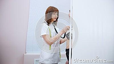 Clínica médica Doctor que trabaja con el golpeo del corazón del estetoscopio de un paciente de la audiencia almacen de metraje de vídeo