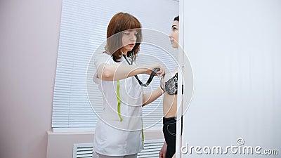 Clínica médica Doctor que trabaja con un estetoscopio que comprueba el golpeo del corazón del paciente metrajes
