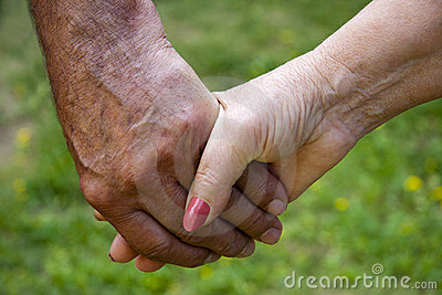 Clasped hands of adults, seniors