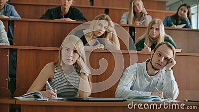 In classe studenti multi etnici ascoltando una lezione e scrivendo nei notebook Smart Young People Study presso stock footage