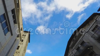 Classic Buildings Sky Fly Focus. Blue sky white clouds fly by betweem two buildings that look classic with a lot of class. Focused on the sky itself stock footage