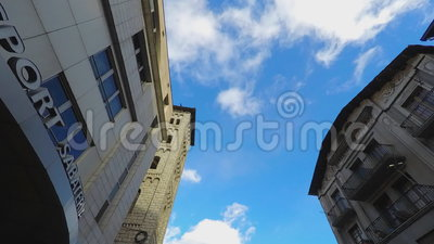 Classic Buildings Sky Fly Focus. Blue sky white clouds fly by betweem two buildings that look classic with a lot of class. Focused on the sky itself stock video footage