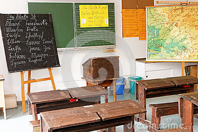 Classroom with old desks, board, and map