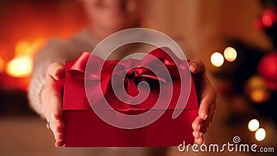 Clausurado video de 4.000 personas de una joven sosteniendo una hermosa caja de regalo roja con un gran lazo y un arco junto al á almacen de video