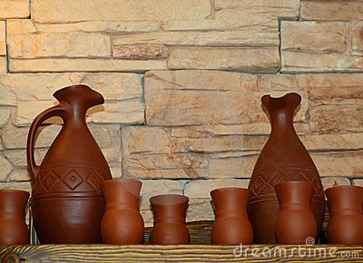 Clay jugs and cups on a shelf
