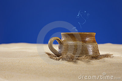 Clay mug with tea or coffee on beach sand