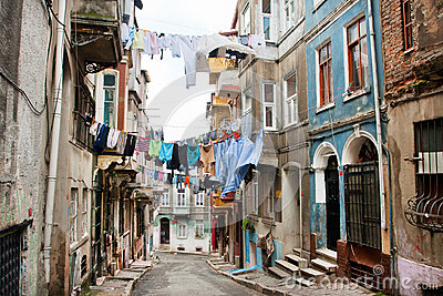 Clean clothes drying on a rope between old houses of narrow street