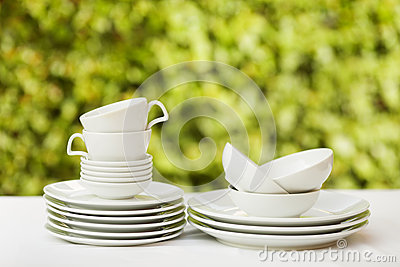 Clean dishes and cups on white tablecloth on green background