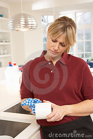 Cleaner Working In Domestic Kitchen