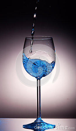 Clear liquid poured into crystal wine glass