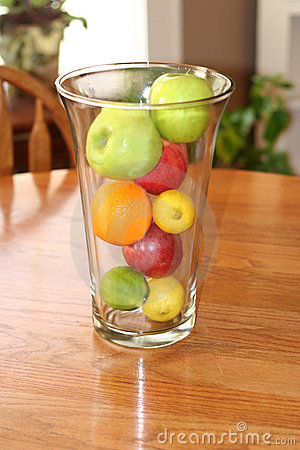 Clear vase with fresh fruit on wooden table