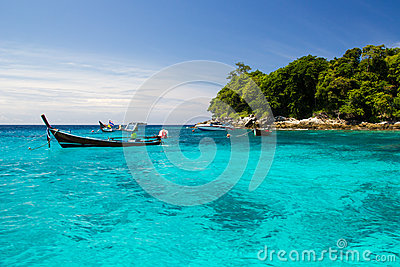 Clear wate,blue sky,and long tail boat