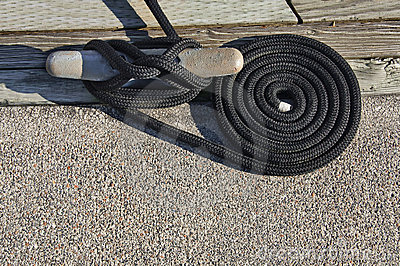 Cleat and black coiled rope at dock.