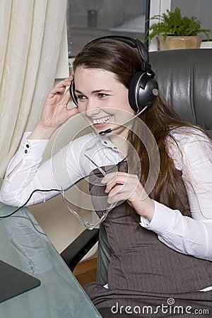 Clerk with headphones sitting in chair in office.