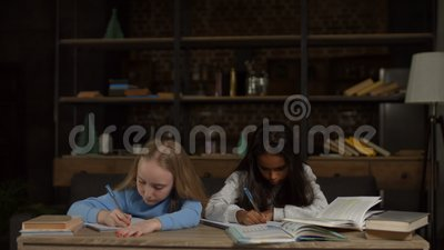 Clever girls doing homework for elementary school stock footage