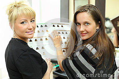 Client and hairdresser with catalog of hair colors