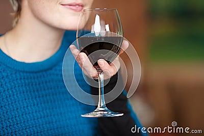 Cliente femenino que celebra la copa de vino roja en el restaurante