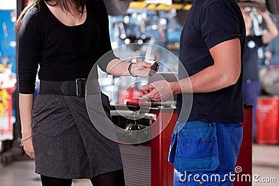 Cliente na loja do mecânico que entrega a chave