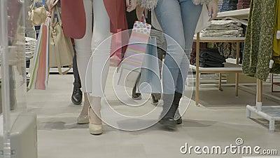 Clientes fêmeas atrativos novos que olham a roupa em uma loja da alameda e que andam lentamente para a câmera - video estoque