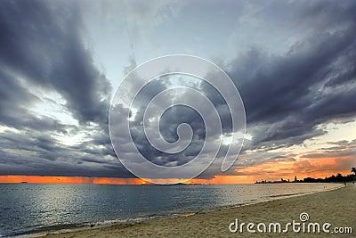 Clima tempestuoso en el mar con puesta del sol
