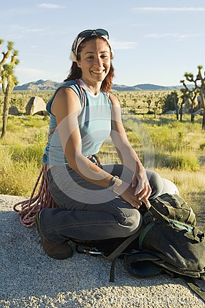 Climber crouching on Boulder with Gear, (portrait)