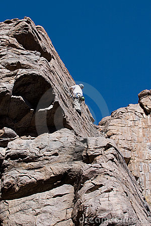 Climber reaching top of climb