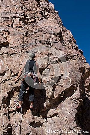 Climber stuck up rock wall