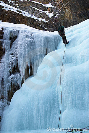 Climber in winter mountains on icefall wall
