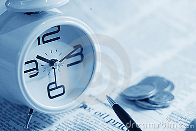 Clock and coin on newspaper