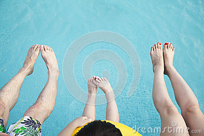 Close on feet on young family in the pool