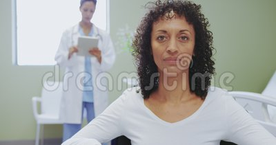 Close-up of African american disabled female patient sitting on wheelchair in the ward at hospital. Caucasian female doctor using digital tablet stock video