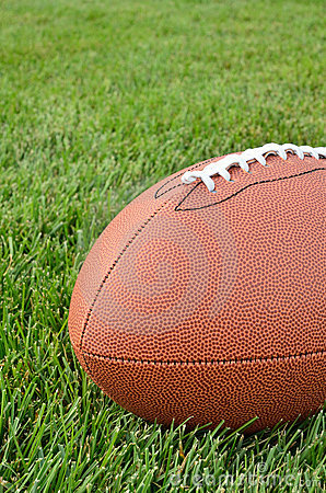 Close-up of an American Football on Grass Field