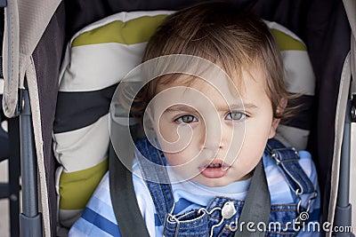 Toddler strapped up in stroller