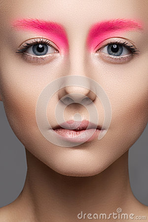 Close-up of beautiful model face with fashion pink make-up, clean skin